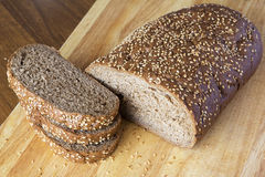 Bread with sesame grains on a wooden table. The cut long loaf Stock Photo