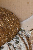 Bread and sieve. Big round wholemeal bread with sunflower seeds and grain; sieve flour in background stock photos