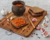 Bread slathered adjika on a cutting board Royalty Free Stock Photos