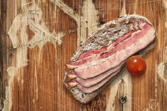 Bread Slice with Bacon Rashers on Old Wooden Background Royalty Free Stock Photo
