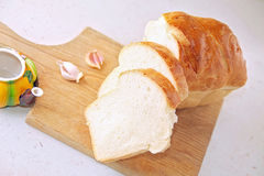 Bread slice and garlic and wooden table Royalty Free Stock Images