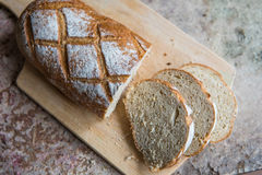 Bread slice on a wooden board. Wheat fresh loaf Royalty Free Stock Images