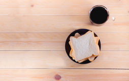 Bread. Sliced bread on black dish and cup of coffee on wooden table Stock Image
