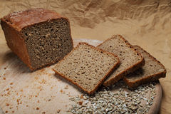 Bread and sliced bread. Wholemeal bread half a loaf and bread slices on chopping board with sunflower seeds Stock Images