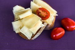 Bread with sliced cheese and tomato on violet background royalty free stock photo