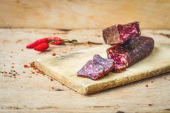 Salami. Bread slices and Bruschetta with different kinds of Salami , peperoncino, fresh onion and spices as a rustic lunch stock photos