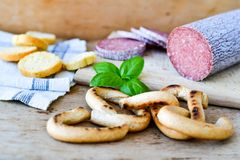 Salami and bread. Bread slices and Bruschetta with different kinds of Salami , peperoncino, fresh onion and spices as a rustic lunch stock photo