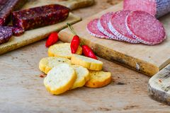 Salami and bread. Bread slices and Bruschetta with different kinds of Salami , peperoncino and spices as a rustic lunch royalty free stock photo