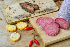 Salami and bread. Bread slices and Bruschetta with different kinds of Salami , peperoncino and spices as a rustic lunch stock photos