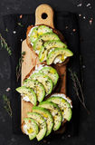 Bread slices with creamy cheese and avocado on wooden cutting board from above for healthy snack. Royalty Free Stock Images