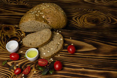 Bread slices decorated with cherry tomatoes with a cup of oil and salt lying on a wooden background. Bread slices decorated with cherry tomatoes and basil with a Stock Photography