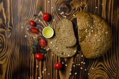 Bread slices decorated with sliced cherry tomatoes with a cup of oil lying on a wooden background. Top view Stock Photo