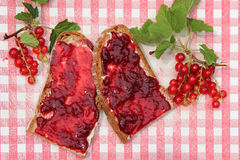 Bread slices with red current jam on nostalgic checkered slat, r. Bread slices with red current jam on nostalgic red and white checkered slat, rustic breakfast stock images