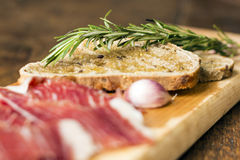 Bread slices with rosemary and serrano ham Royalty Free Stock Photography