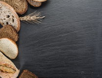 Bread slices, a wheat and a knife on the black desk. Royalty Free Stock Images