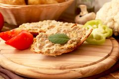 Bread smeared with aubergine salad. Slice of bread smeared with eggplant salad and a sprig of basil leaf,green pepper and tomato slices Royalty Free Stock Photography