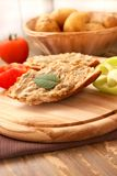 Bread smeared with aubergine salad. Slice of bread smeared with eggplant salad and a sprig of basil leaf,green pepper and tomato slices Stock Image