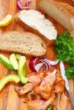 Making smoked salmon sandwich vertical stock photo