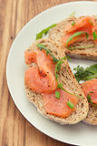 Bread with smoked salmon on white plate Royalty Free Stock Images