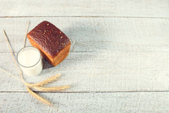 Bread with spikelets of wheat and glass of milk on a boards. Stock Photos