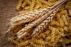 Bread spikes and pasta on rough fabric background stock images