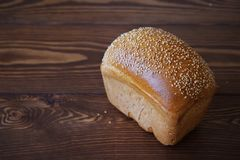 Bread sprinkled with sesame seeds on a wooden table. The concept of healthy organic food. Farm products or homemade cakes. Copy stock images