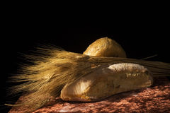 Bread and stalks of wheat. Whole loafs of bread garnished with stalks of wheat. Black background stock photo