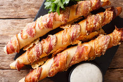 Bread sticks baked with bacon and cheese close-up on the table. Royalty Free Stock Photography