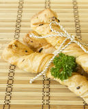 Bread sticks with parsley on a wooden stand. Bread sticks puff pastry with parsley, sesame seeds and chives tied with rope Royalty Free Stock Photography