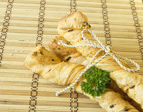 Bread sticks with parsley on a wooden stand. Bread sticks puff pastry with parsley, sesame seeds and chives tied with rope Stock Image