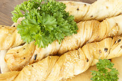 Bread sticks with parsley on a wooden stand. Bread sticks puff testas parsley, sesame seeds and onion Stock Photography