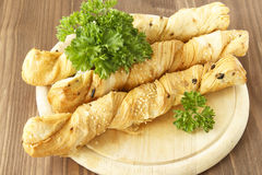 Bread sticks with parsley on a wooden stand. Bread sticks puff testas parsley, sesame seeds and onion Royalty Free Stock Image