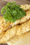 Bread sticks with parsley on a wooden stand. Bread sticks puff testas parsley, sesame seeds and onion Royalty Free Stock Images