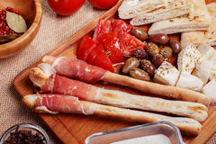 Bread sticks with prosciutto Cured Meat on a wooden cutting boar. D with pita bread, red tomatoes, olives, cheese and other ingredients for a lunch snack Royalty Free Stock Image
