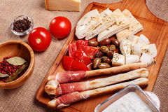 Bread sticks with prosciutto Cured Meat on a wooden cutting boar. D with pita bread, red tomatoes, olives, cheese and other ingredients for a lunch snack Royalty Free Stock Photos