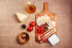 Bread sticks with prosciutto Cured meat. On a wooden cutting board with pita bread, red tomatoes, olives, cheese and other ingredients for a lunch snack Stock Images