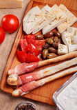 Bread sticks with prosciutto Cured meat. On a wooden cutting board with pita bread, red tomatoes, olives, cheese and other ingredients for a lunch snack Stock Image