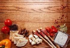 Bread sticks with prosciutto Cured Meat on a wooden table. With pita bread, red tomatoes, olives, cheese and other ingredients for a lunch snack Stock Photo