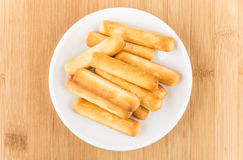 Bread sticks in saucer with salt on wooden table Royalty Free Stock Photos