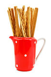 Bread sticks to milkman. Bread sticks in red milkman with a light shadow on a white background Royalty Free Stock Photography