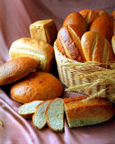 Bread still life. A close up portrait of some loaves of freshly baked bread displayed in a small wicker basket. Some of the loaves are cut into slices Royalty Free Stock Image