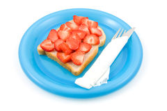 Bread with strawberry on colorful blue plate Stock Photos