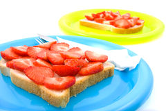 Bread with strawberry on colorful plates Royalty Free Stock Photos