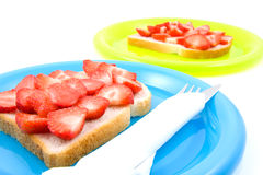 Bread with strawberry on colorful plates Royalty Free Stock Images