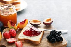 Bread with strawberry jam. And ripe berries on grey wooden table stock photo