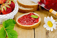 Bread with strawberry jam and chamomile on board Stock Photos