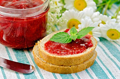 Bread with strawberry jam and daisies on a napkin Stock Photos
