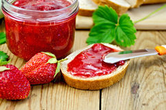 Bread with strawberry jam and a knife on board Royalty Free Stock Photo