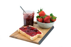 Bread with strawberry jam on a wooden board. royalty free stock image