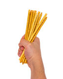 Bread Straws in the hand. On a white background Stock Photos